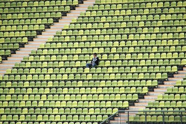 Man sitting alone in stadium